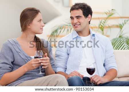 Couple having a glass of red wine while looking at each other - stock photo