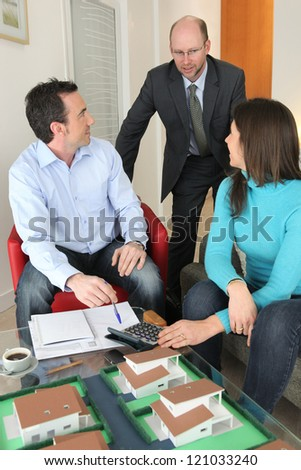 Couple having a meeting with their architect - stock photo