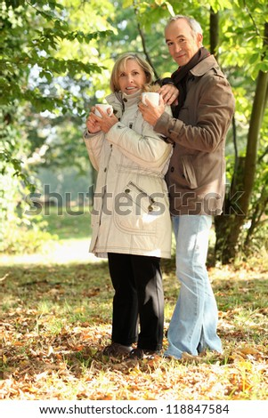 Couple having a mug of hot chocolate in the forest - stock photo