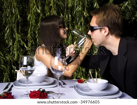 Couple having a romantic lunch in the garden enjoying wine