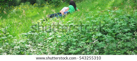 Couple having a sexual encounter in the grass outside.