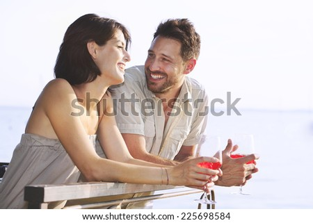 Couple having a spritz time with a lake view - stock photo