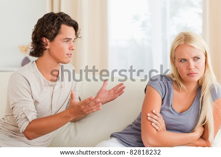 Couple having an argument in their living room - stock photo