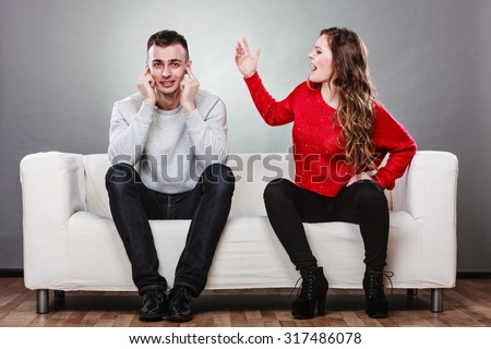 couple having argument - conflict, bad relationships. Angry fury woman screaming man closing his ears. - stock photo