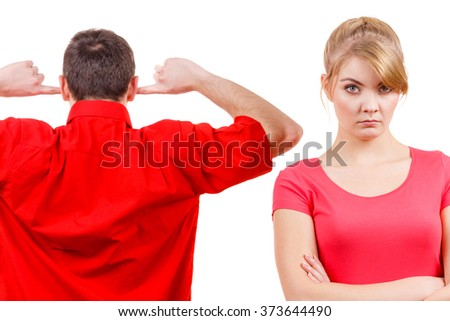 Couple having argument, conflict bad relationships. Angry offended woman and man standing with fingers in his ears not listening - stock photo