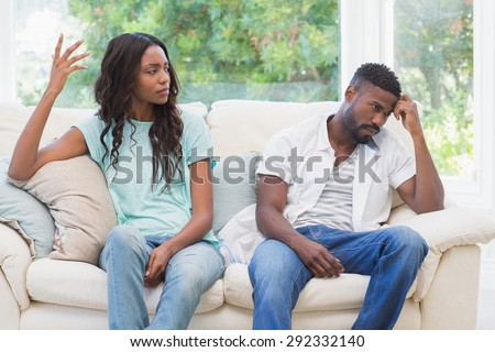 Couple having argument on the couch at home in the living room - stock photo
