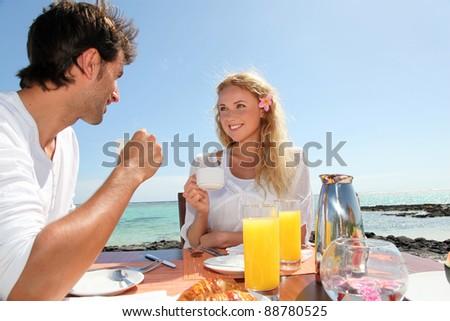 Couple having breakfast by blue lagoon - stock photo