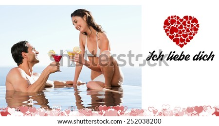 Couple having cocktails in the pool against ich liebe dich - stock photo
