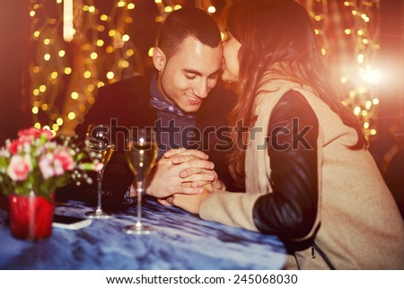 Couple having dinner with champagne glass on a table - stock photo