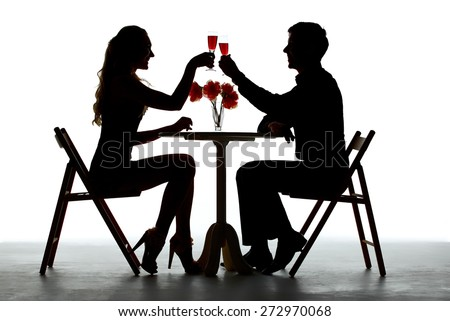 Couple Having Dinner With Wine Glass On Table. silhouettes on white background - stock photo