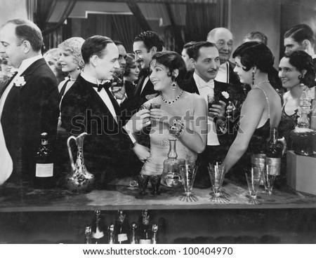 Couple having drink at crowded bar - stock photo