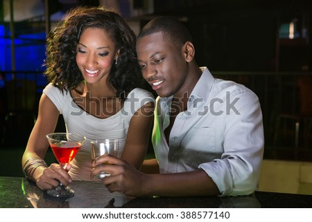 Couple having drinks at bar counter in bar - stock photo