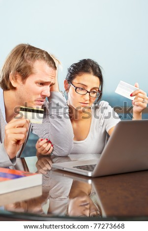 Couple having financial, look depressed holding credit card in front of laptop