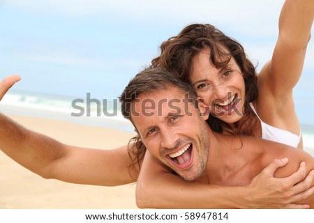 Couple having fun at the beach - stock photo