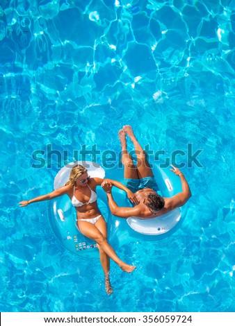 Couple having fun at the swimming pool - stock photo