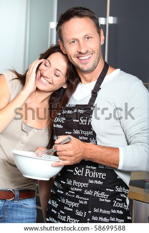 Couple having fun cooking at home - stock photo