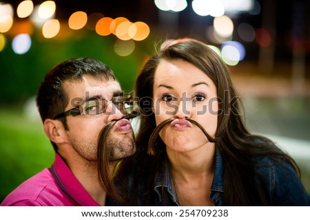 Couple having fun in street at night - making moustache with their hair - stock photo