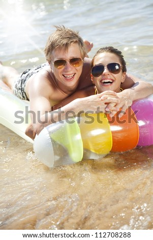 couple having fun on a lilo - stock photo