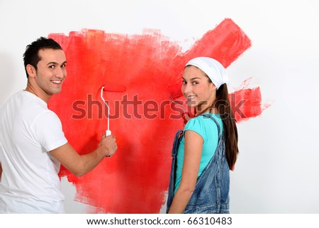 Couple having fun painting their new house