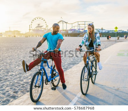 couple having fun riding bikes together at santa monica california