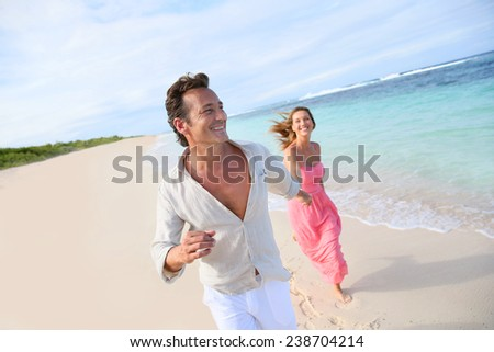 Couple having fun running on a caribbean beach  - stock photo