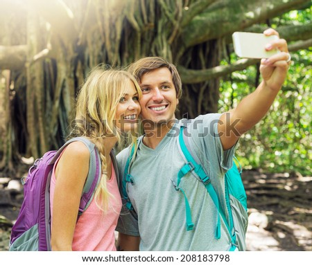Couple having fun together outdoors. Taking self portrait with camera phone on hike. - stock photo