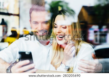 Couple having fun using smartphone at cafe