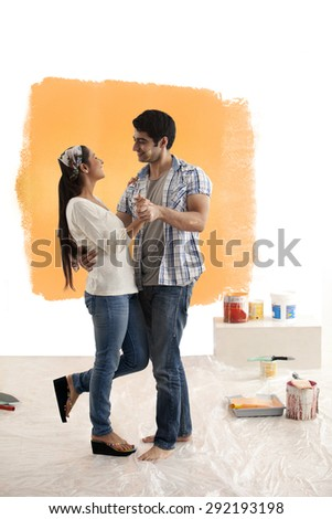 Couple having great time dancing together at their new home - stock photo