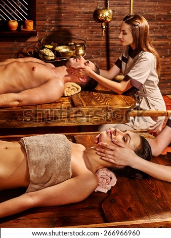 Couple  having oil Ayurveda spa treatment. Wooden table.Facial massage. - stock photo