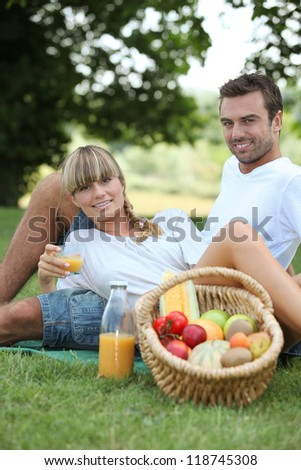 couple having picnic in the park - stock photo