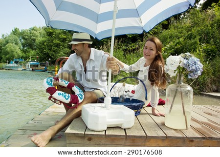 Couple Having Picnic on River Breakwater and Man Throwing Lifebuoy - stock photo