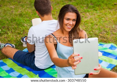 Couple having picnic. Pretty girl is taking selfie, Man reads.