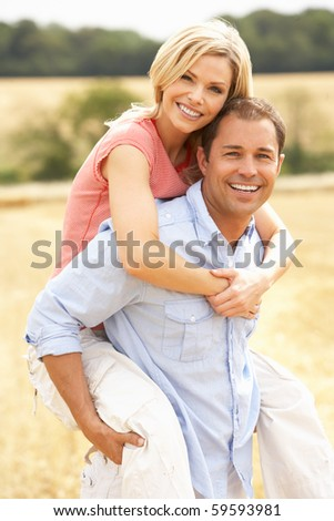 Couple Having Piggyback In Summer Harvested Field - stock photo