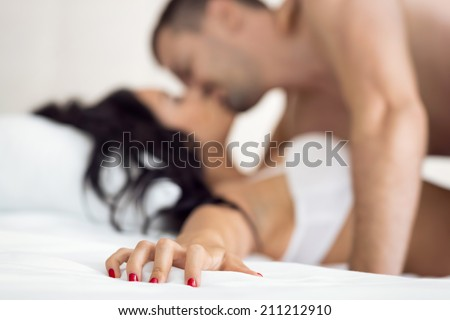 Couple having sex, female hand grabbing sheet - stock photo