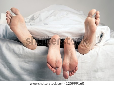 Couple having sex in bed under sheets. - stock photo