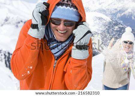 Couple having snowball fight together