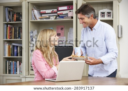 Couple Having Working Lunch In Home Office Together