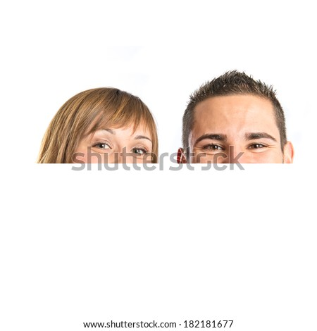 Couple hiding behind placard over white background