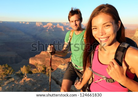 Couple hikers in Grand Canyon. Aspirational lifestyle image of happy young people hiking the South Rim trail of Grand Canyon. Multiethnic couple, Asian woman, Caucasian man. - stock photo