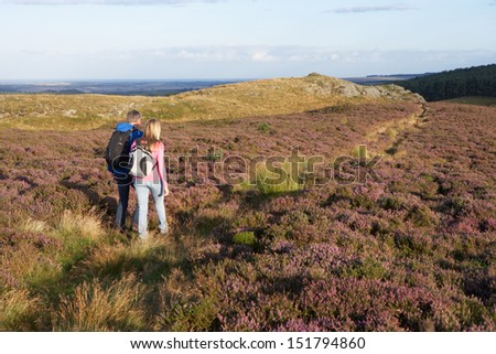 Couple Hiking Across Moorland Covered With Heather - stock photo