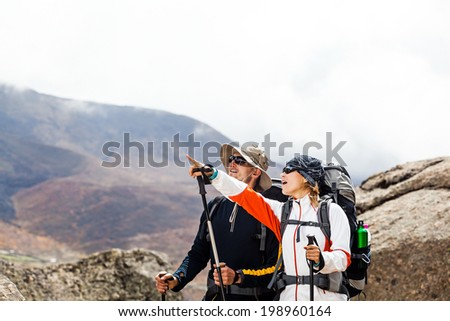 Couple hiking and trekking in mountains, Nepal. Man and woman walking and climbing in Himalayas, autumn outdoors nature, sport and exercising. Healthy lifestyle, fitness outdoors. - stock photo