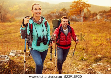 Couple hiking during autumn vacation with sticks and backpacks