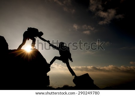 Couple hiking help each other silhouette in mountains - stock photo