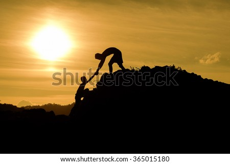 Couple hiking help teamwork and trust silhouette in mountains, sunset and ocean. Male and woman hiker helping each other on top mountain looking at beautiful night landscape motivation and inspiration - stock photo