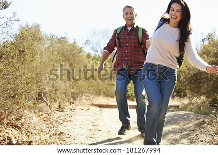 Couple Hiking In Countryside Wearing Backpacks - stock photo