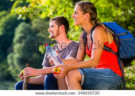 Couple hiking in summer drinking water - stock photo