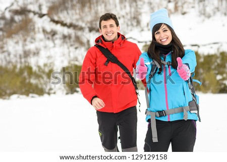 Couple hiking on snowy mountain nature on winter vacations outdoors. Happy hiker traveler woman success with thumbs up. - stock photo