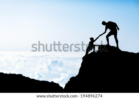 Couple hiking teamwork partners help each other silhouette in mountains, motivation and inspiration. Man and woman hiker helping hand trust on top of mountain climbing, beautiful sunset landscape. - stock photo