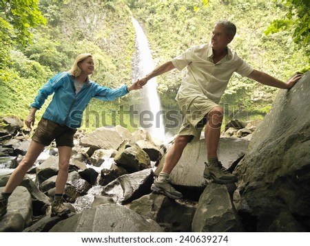Couple Hiking to a Waterfall - stock photo