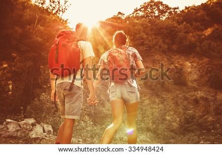 Couple hiking together on beautiful sunset. - stock photo